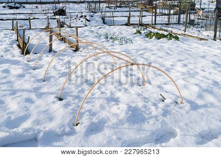 Plastic Frame Of A Small Greenhouse Outside In The Snow