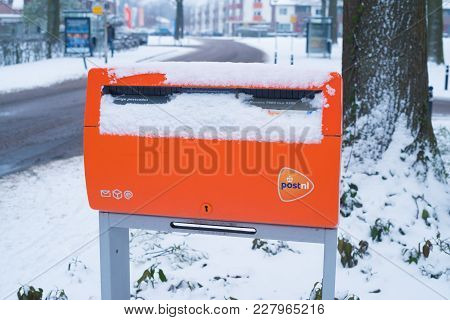 Oldenzaal, Netherlands - January 7, 2017: Official Orange Postbox Covered With Fresh Snow