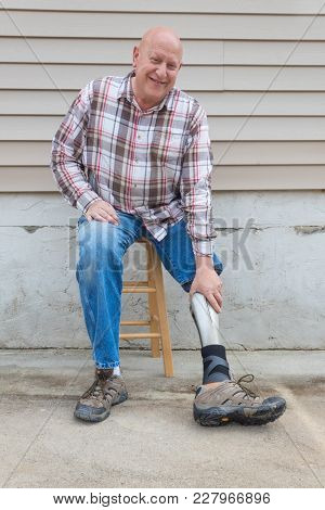 Amputee Man On A Stool Looking Forward Reaching Down To Adjust Prosthetic Leg, Copy Space, Vertical