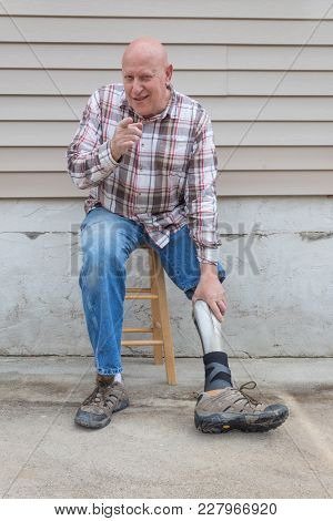 Amputee Man On A Stool Looking Forward Pointing At The Camera, Reaching Down To Adjust Prosthetic Le