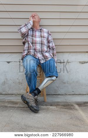 Amputee Man Sitting On Stool With Prosthetic Leg Crossed, Looking Up With Hand To Side Of Face, Copy