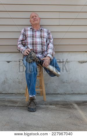 Seated Amputee Man With Prosthetic Leg Crossed, Holding With Both Hands, Copy Space, Vertical Aspect