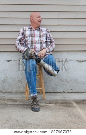 Smiling Amputee Man Sitting On A Stool, Holding Crossed Prosthetic Leg At The Ankle, Copy Space, Ver