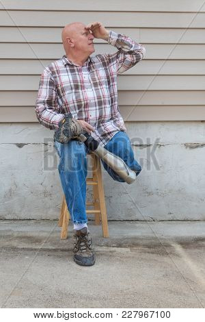 Smiling Amputee Man Sitting On A Stool, Prosthetic Leg Crossed, Shading Eyes Looking Up, Copy Space,