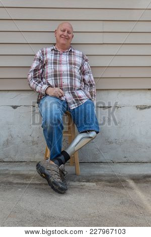Smiling Amputee Man, Prosthetic Leg Forward, Seated, Copy Space, Vertical Aspect