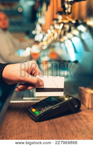 Man Using Payment Terminal. White Credit Card. Hand Use Credit Card. Bar Table. The Beer Taps In A P