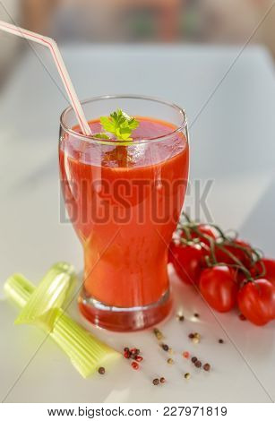 Tomato Juice In A Glass With Celery And Tomatoes On A Branch
