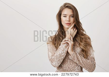 Hot Feminine Caucasian Female Softly Touching Cheek While Standing In Seducing Pose Over Gray Backgr
