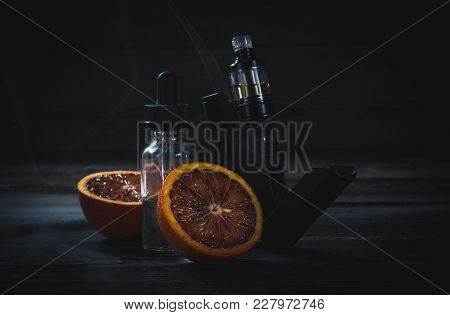 Black Vaporizer In The Smoke With Sliced Orange And The Liquid