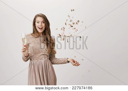Feminine Caucasian Model In Luxurious Evening Dress Tossing Up Confetti While Raising Glass Of Champ