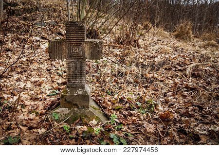 Old Tombstone Cross Of The First World War Overgrown With Moss And Old Leaves In The Autumn Forest
