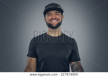 Portrait Of Smiling  Bearded Male In Baseball Cap Isolated On Grey Background.