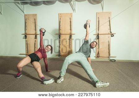 Young Couple Workout Kettlebell Fitness Exercise In The Gym, Selective Focus
