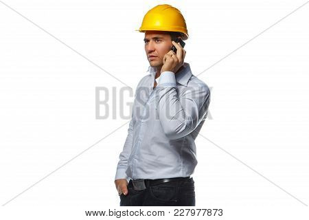 Male In Yellow Safe Helmet Talking By Smartphone. Isolated On A White Background.