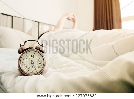 Man Stretched In Bed After The Alarm Clock In The Sunlight Morning. Man Stretched In Bed After The A