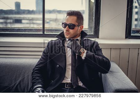 A Man In Sunglasses And Black Gloves Sitting On The Sofa.