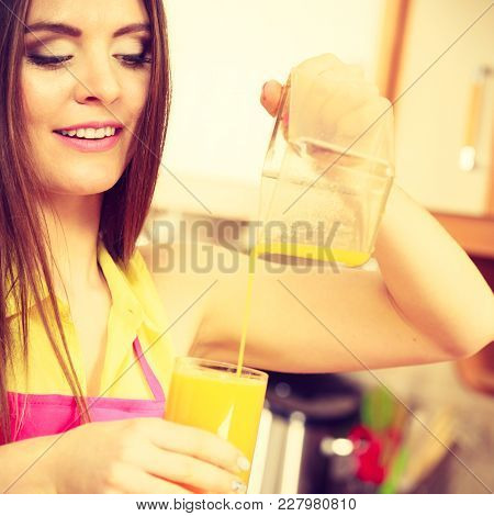 Woman Young Housewife In Kitchen Making Fresh Orange Juice In Juicer Machine, Pouring Drink From Jug