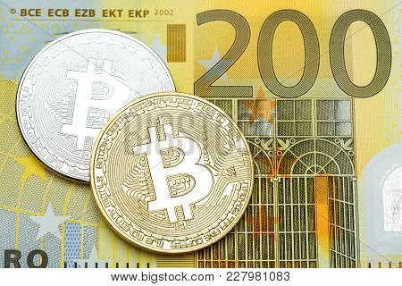 Silver And Golden Bitcoin On 200 Euro Banknote Background. High Resolution Photo.
