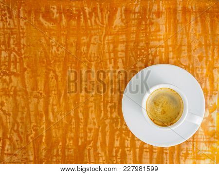 Black Frothy Coffee With Foam In White Cup With Plate On Bright Copper Metal Table, Top View, Empty