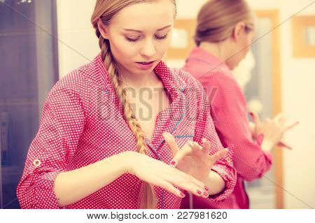 Body Care Concept. Young Woman Wearing Pink Pajamas Applying Moisturizing Hand Cream On Hands And Na