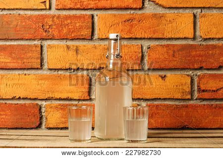 The Bottle Of Vodka And Two Shot Glasses Outdoor. Bottle And Shot Glass Filled With Clear Liquid
