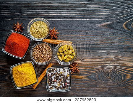 Set Of Spices On A Dark Brown Textured Wooden Table - Coriander Seeds, Ground Red Pepper, Salt, Blac