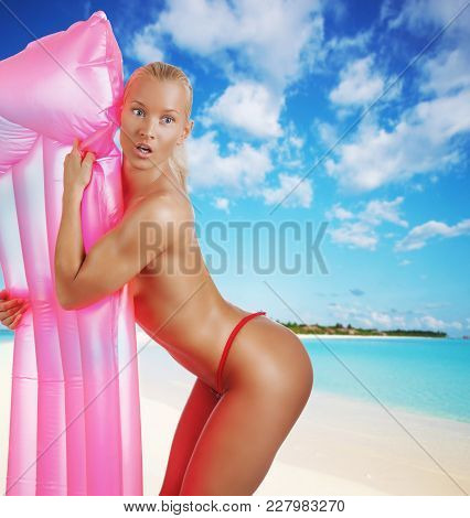 Sexual Blond Woman Posing With A Pink Water Mattress.