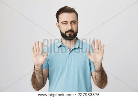 Portrait Of Calm Adult Man With Beard Raising His Palms And Looking At Camera, Standing Over Gray Ba