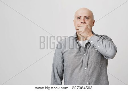 Stressed Frustrated Bald Bearded Male Dressed In Casual Clothes Closes His Mouth With Hand In Terror