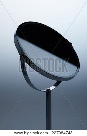 Close-up Shot Of Cosmetic Mirror With Stand On Grey