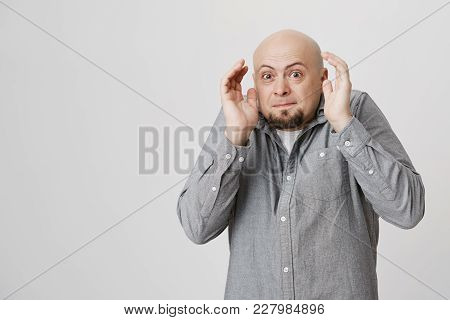 Emotional Caucasian Bald Bearded Man In Gray Shirt Looking At Camera With Popped Eyes, Holding Hands