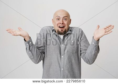 Excited Bald Male With Beard In Casual Shirt Exclaiming, Looking At Camera In Amazement With Opened