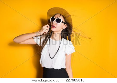 Attractive Young Girl In Fashion Hat And Black Sunglasses Posing On Yellow Background, Hair Flapping