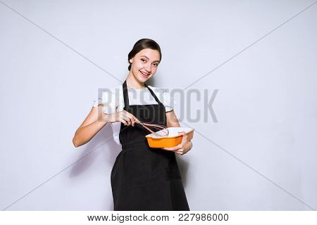 Beautiful Young Woman Cook In A Black Apron Preparing A Delicious Meal, Smiling