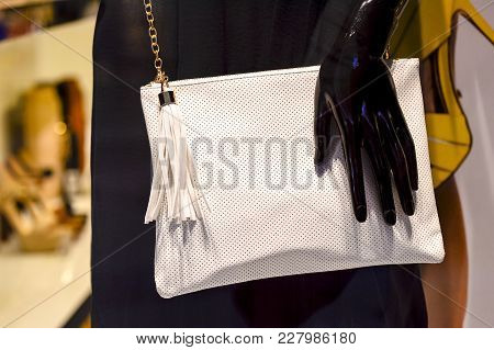 Women's Handbag White Color Small Size With Shoulder Strap On The Black Dummy With A Hand Closeup