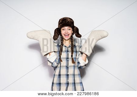 Happy Beautiful Russian Girl In Warm Fur Hat Holds Winter Felt Boots