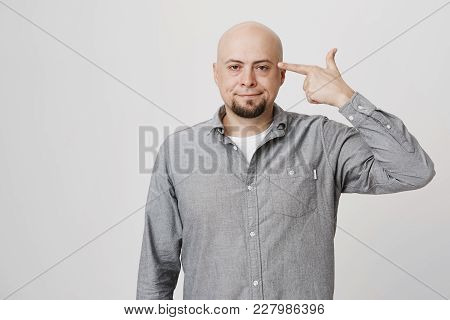 Unhappy Bald Bearded Man Curves Lips And Makes Suicide Gesture, Being Tired Of Everything, Shoots In