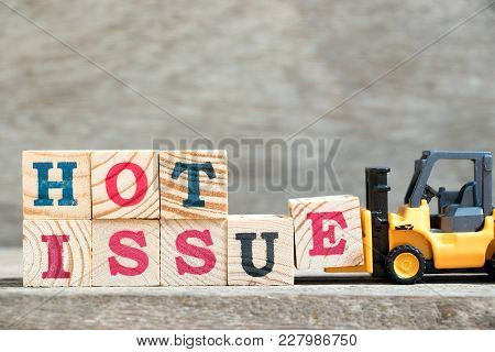 Toy Forklift Hold Letter Block E To Complete Word Hot Issue On Wood Background