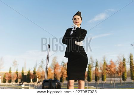 A Luxurious Young Woman Stewardess In Uniform With A Suitcase Waiting For Her Plane, Thinking About