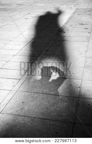 The Photographer Makes His Photos With A Camera Using The Shadow Of A Monument. Street Photography.