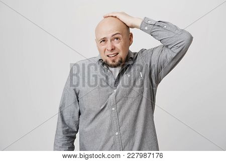 Pensive Bald Bearded Man In Grey Shirt Posing Against Gray Background, Frowns Face, Looks Thoughtful