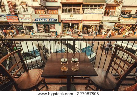 Kandy, Sri Lanka - Jan 6, 2018: Table Of Local Cafe On Busy City Street With Markets And Food Stores