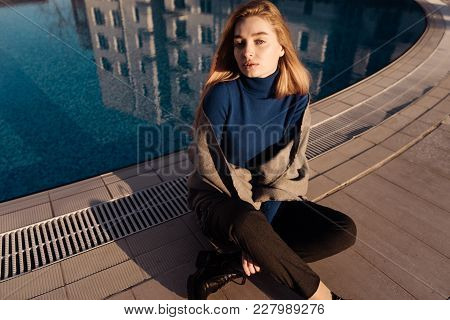 Beautiful Attractive Blonde Girl In Blue Sweater Sits By The Blue Pool, Enjoys The Spring Sun And Lo