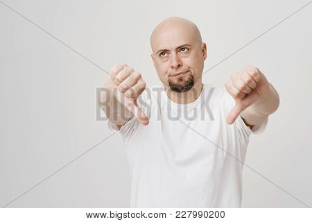 Portrait Of Bothered Annoyed Bald Caucasian Bearded Man Showing Thumbs Down, Giving Negative Opinion
