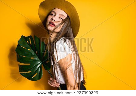 Attractive Beautiful Long-haired Girl In Fashion Hat Posing On Yellow Background, Holding A Green Le