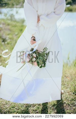 Bride In Nature With A Beautiful Wedding Bouquet