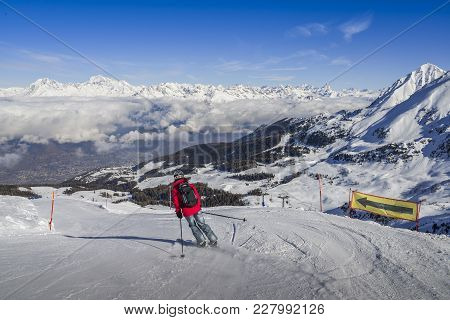 Pila, Aosta, Italy - Feb 19, 2018: One Skier In Jeans Going Downhill A Piste With Panoramic View Of