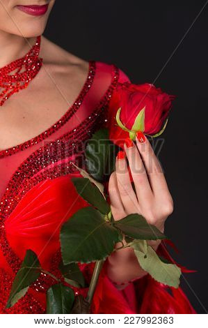 Rose Flower In Female Hand In Red Dress On Dark Background. Love, Desire, Passion. Valentine Present