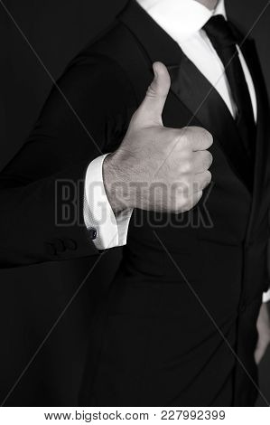 Hand Show Thumbs Up In Male Suit On Dark Background. Positive Hand Gesture, Sign, Symbol. Approval,