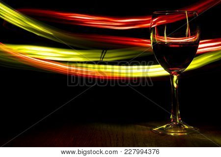 A Glass Of Wine In Night Club. Red And Yellow Blurred Bands. The Light Effect.